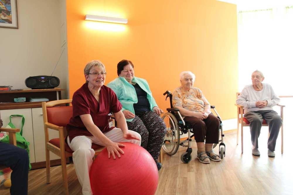 Eine Mitarbeitende sitzt auf einem Stuhl und hat einen großen Gymnastikball vor sich. Rechts von ihr sitzt eine Bewohnerin auf einem Stuhl, eine weitere in ihrem Rollstuhl.