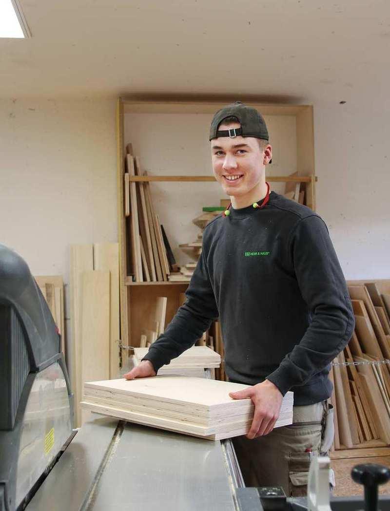 Ein junger Mann legt mehrere Holzplatten auf eine Maschine.