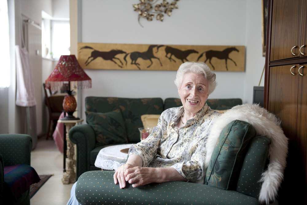 Eine ältere Frau sitzt in einem Sessel.