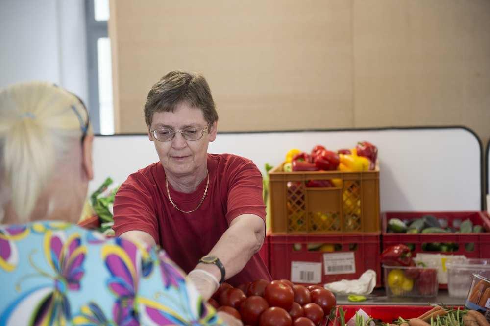 Eine Mitarbeiterin der Tafel gibt Tomaten und Paprika aus.