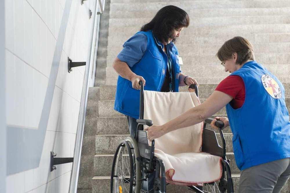 Zwei Mitarbeiterinnen der Bahnhofsmission tragen einen Rollstuhl eine Treppe hinauf.