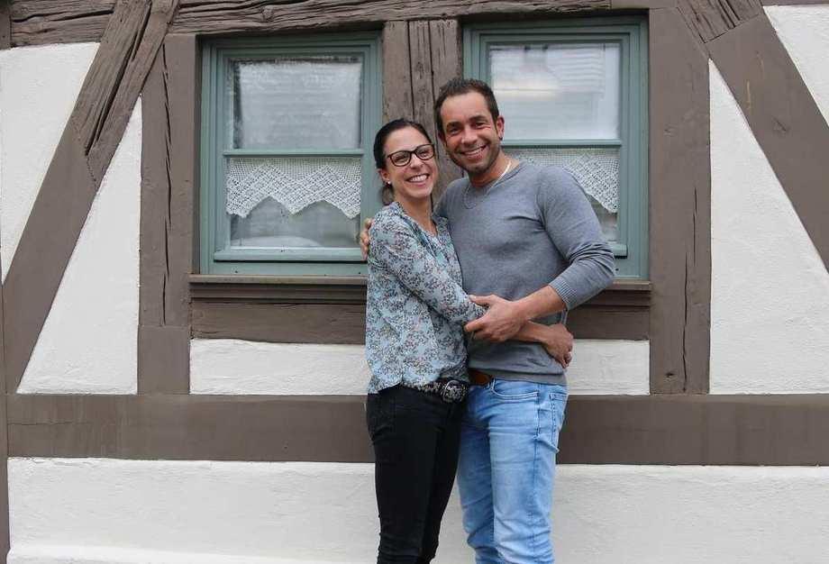 Eine Frau und ein Mann stehen engumschlungen vor der Wand eines Fachwerkhauses.