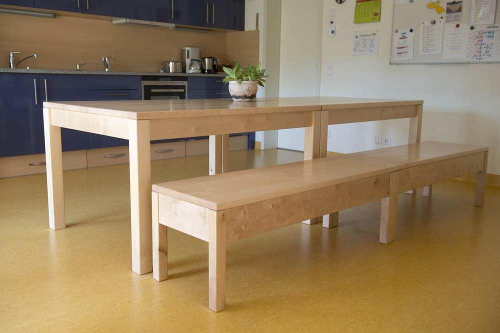 Tisch mit Sitzbank aus hellem Holz. Dahinter eine Kücheneinrichtung.