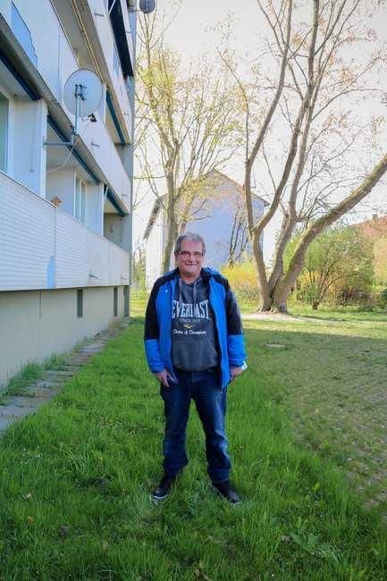 Ein Mann steht vor einem Haus auf der Wiese.