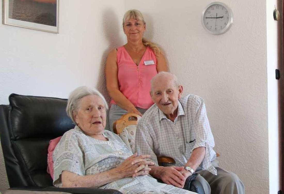 Ein älteres Ehepaar sitzt in ihrem Wohnzimmer. Hinter ihnen steht eine Pflegekraft.
