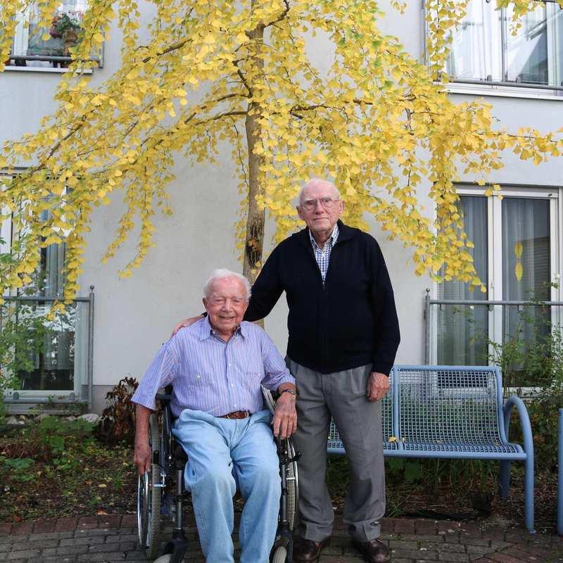 Zwei ältere Männer sind im Außenbereich der Diakonie Sophienstraße. Ein Mann sitzt im Rollstuhl, der andere steht neben ihm. Hinter den beiden befindet sich eine Bank und eine große Birke.