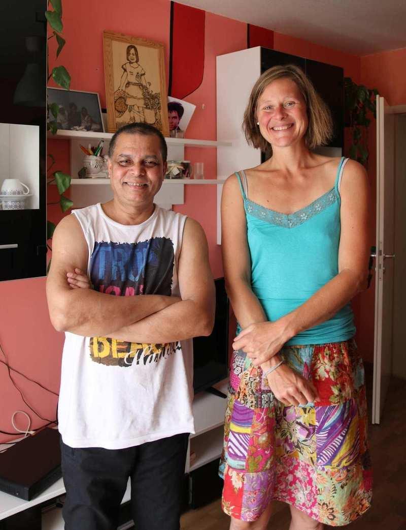 Ein Mann und eine Frau stehen nebeneinander in einem Wohnzimmer. Der Mann trägt ein ärmelloses T-Shirt und hat die Arme vor der Brust verschränkt. Die Frau hat ein blaues Oberteil und einen bunten Rock.