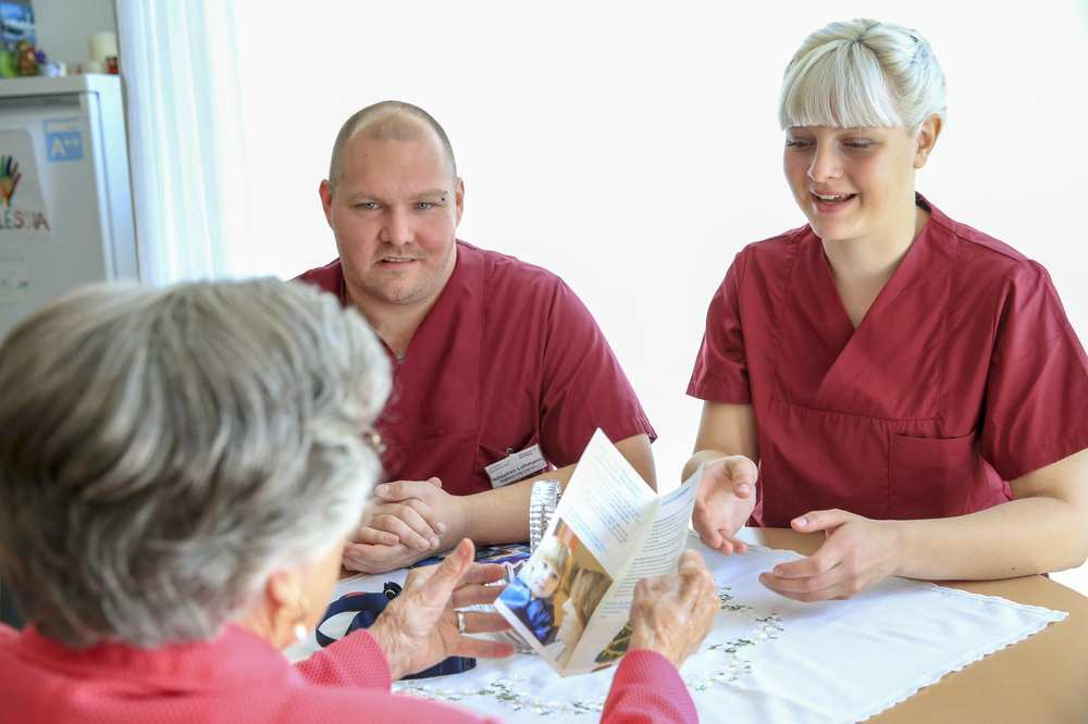 Zwei Pflegekräfte unterhalten sich mit einer älteren Frau.