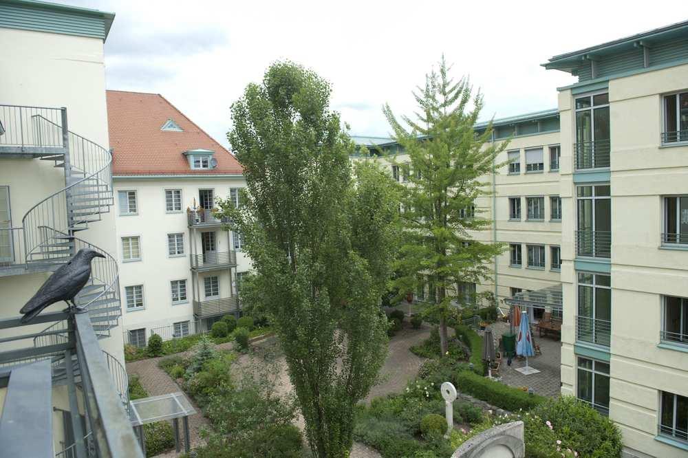 Blick vom Dach eines gegenüberliegenden Gebäudes auf die Fassade des Hauses.