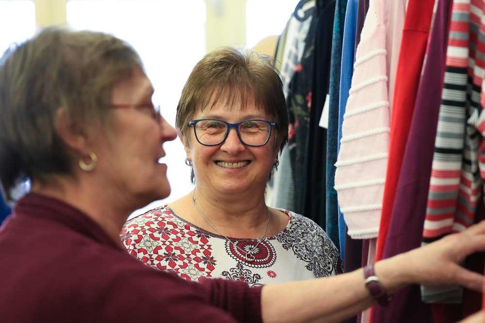 Zwei Frauen stehen an einer Stange mit aufgehängten Kleidungsstücken. Eine der Frauen begutachtet einen Pullover.