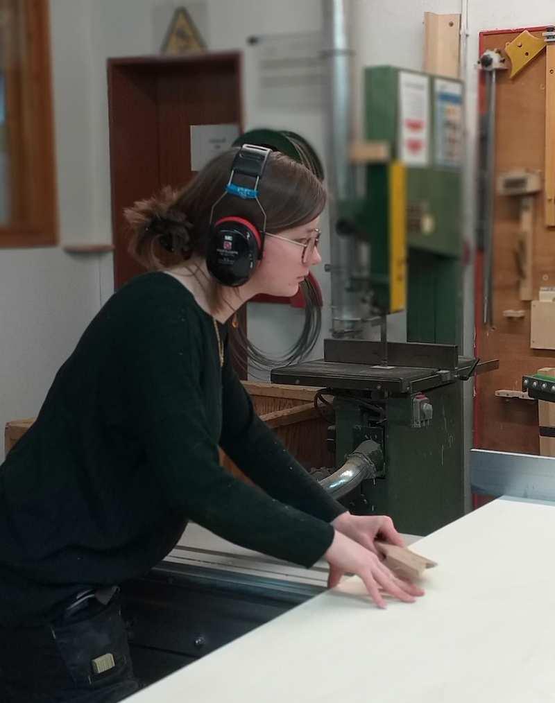 Eine Frau mit Ohrschützern steht an einer Maschine.