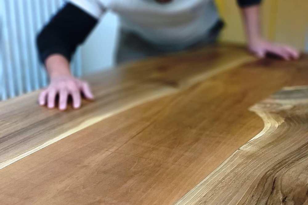 Eine dunkel gemaserte Platte eines Tisches aus Nussbaum.