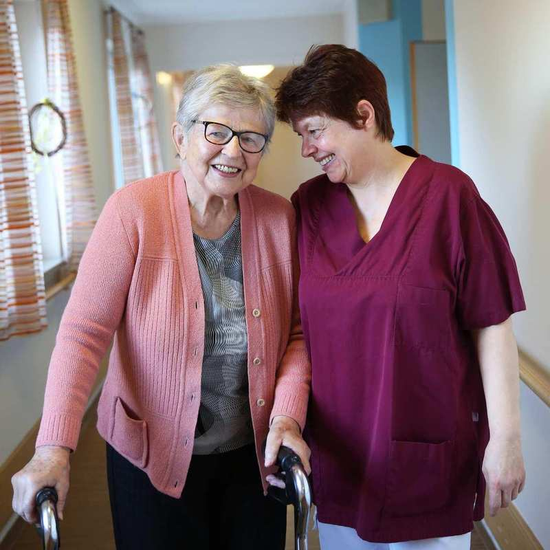 Eine ältere Bewohnerin mit Rollator und eine Pflegekraft stehen vertrauensvoll aneinandergelehnt.