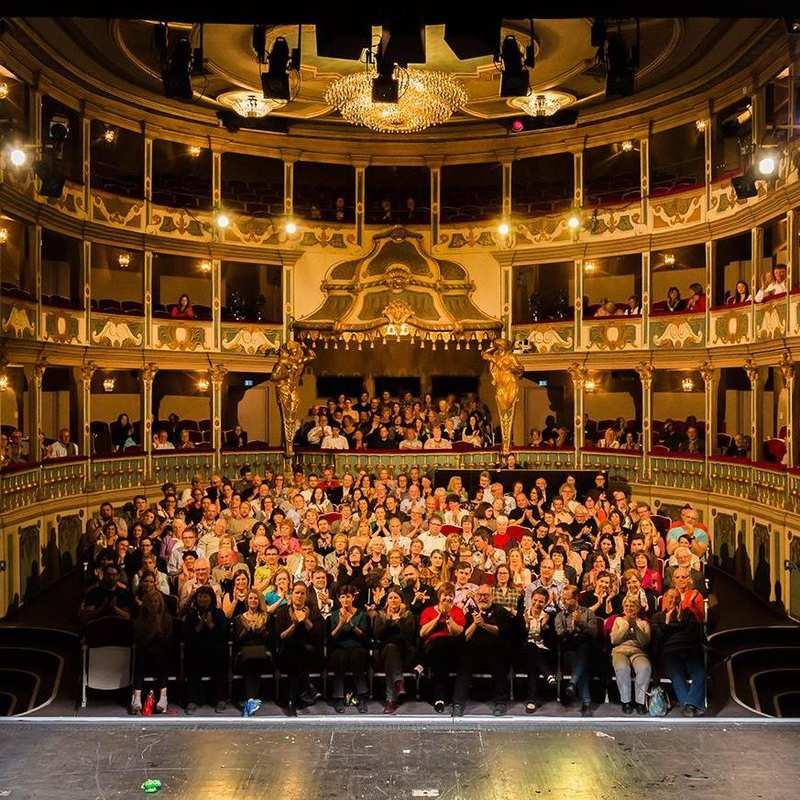 Das hell erleuchtete Markgrafentheater Erlangen mit voll besetztem Parkett und Rängen. Die Besucherinnen klatschen.