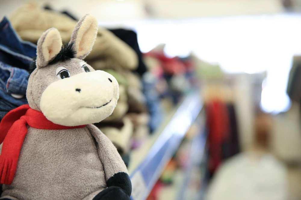 Ein Plüschtier Esel sitzt vor einem Stapel zusammengelegter Kleidung.