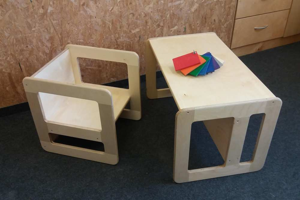 Ein kleiner Stuhl und ein Tischchen aus hellem Holz.