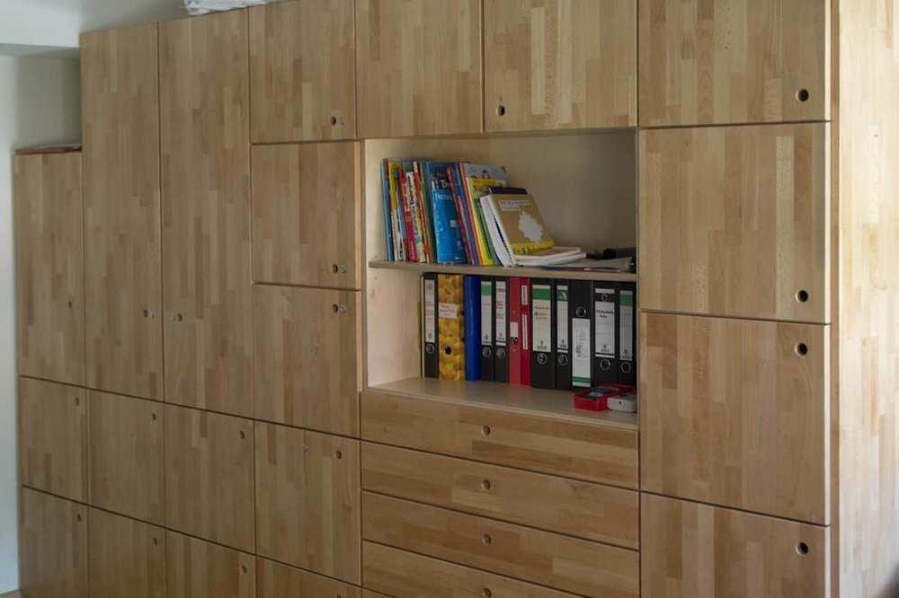 Ein aus fünf Ebenen bestehender Wandschrank aus hellem Holz.