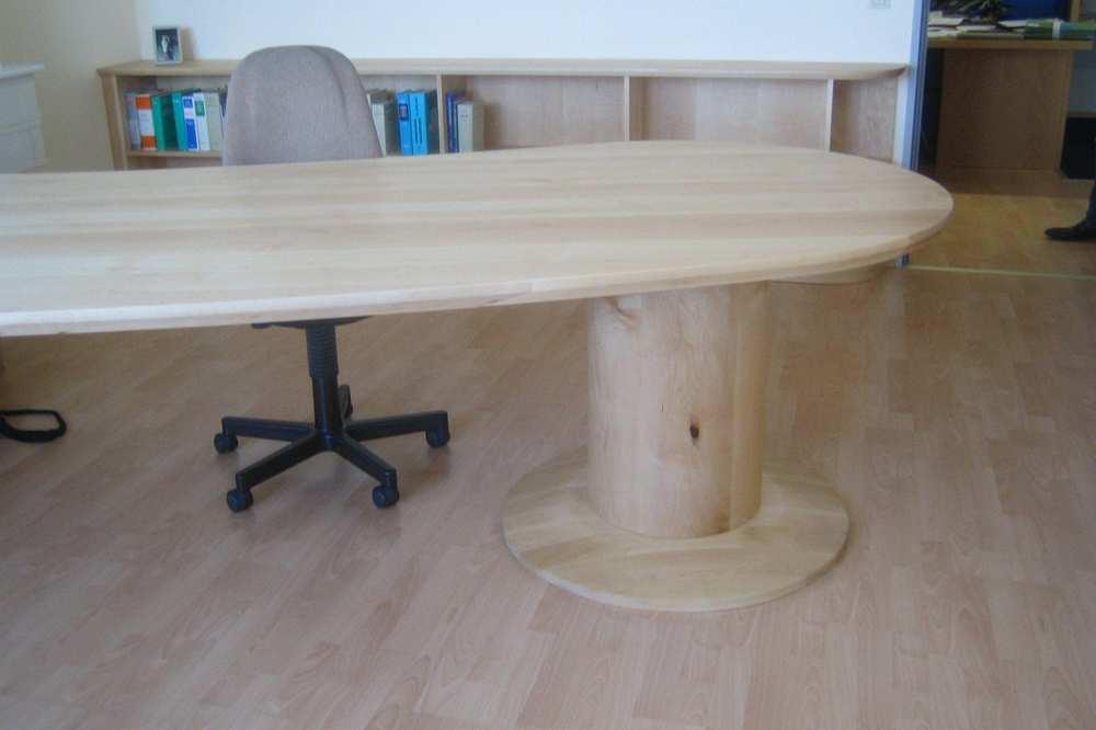 Eine ovale, längliche Schreibtischplatte mit einem runden Fuß aus hellem Holz.