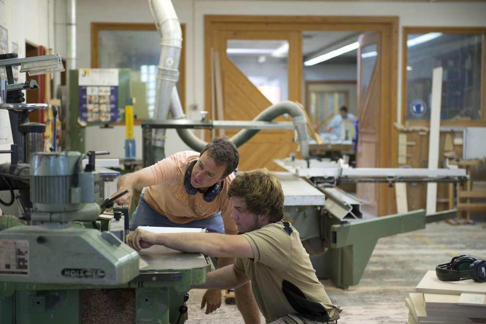 Zwei Männer stellen eine Maschine ein.