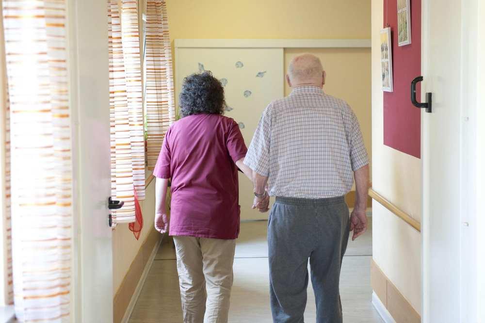Eine Pflegekraft und ein älterer Mann gehen einen Flur entlang.