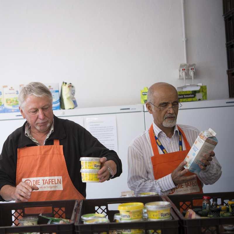 Drei Mitarbeitende mit organgenen Tafelschürzen sortieren Lebensmittel in Plastikboxen.