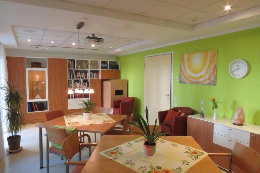 Ein großer Raum mit zwei Tischen und farbenfrohen Malereien an der Wand.