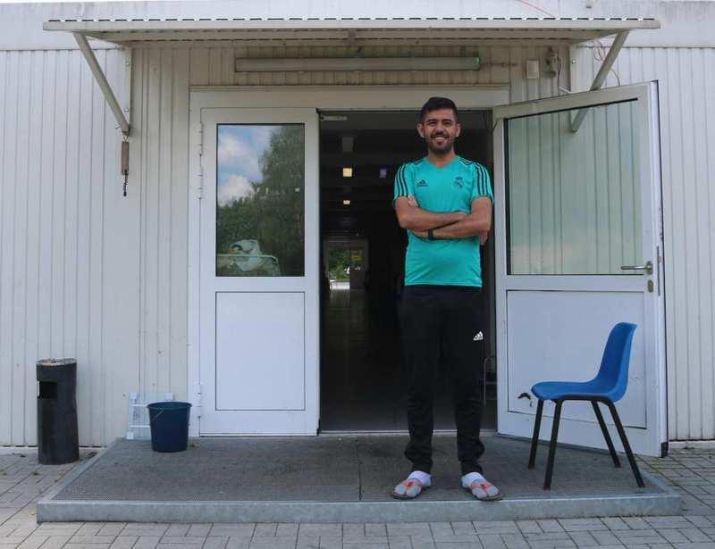 Ein junger Mann mit T-Shirt und Jogginghose steht vor einer geöffneten Tür.