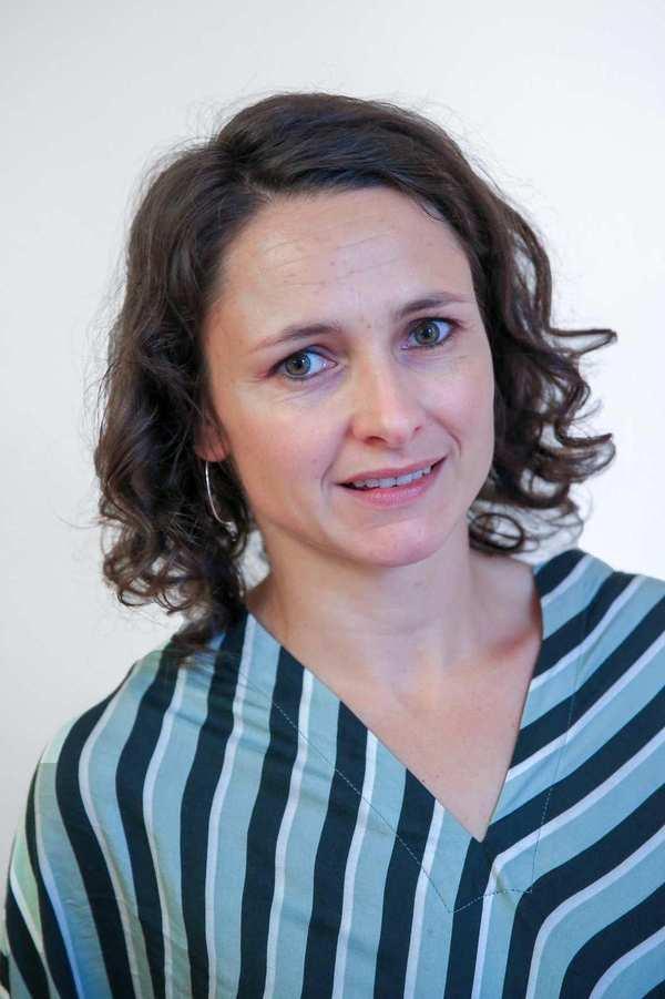 Juliane Siegel. Eine Frau mit brauen, schulterlangen gelockten Haaren.