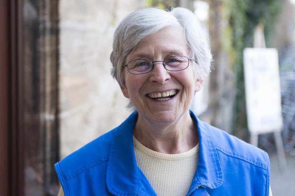Eine ältere Mitarbeiterin der Bahnhofsmission mit Brille. Sie lacht.