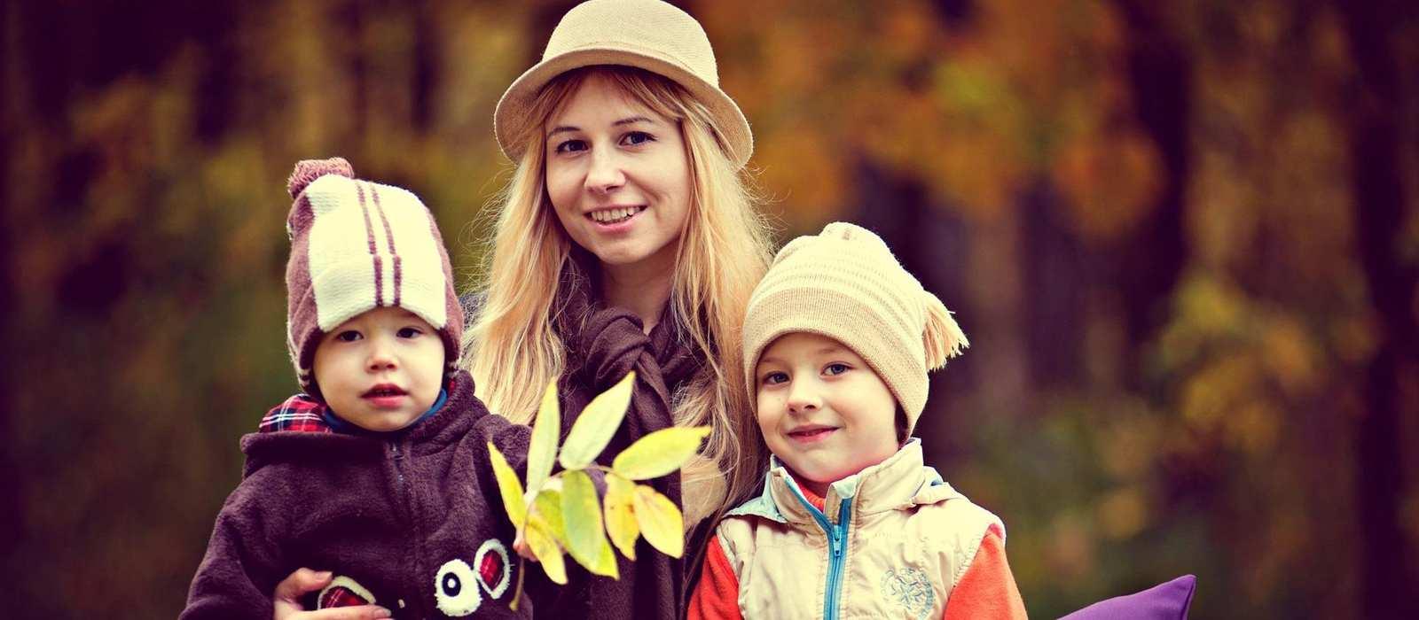 Eine junge Frau hält zwei kleinere Kinder in den Armen. Im Hintergrund ist ein herbstlicher Laubwald.