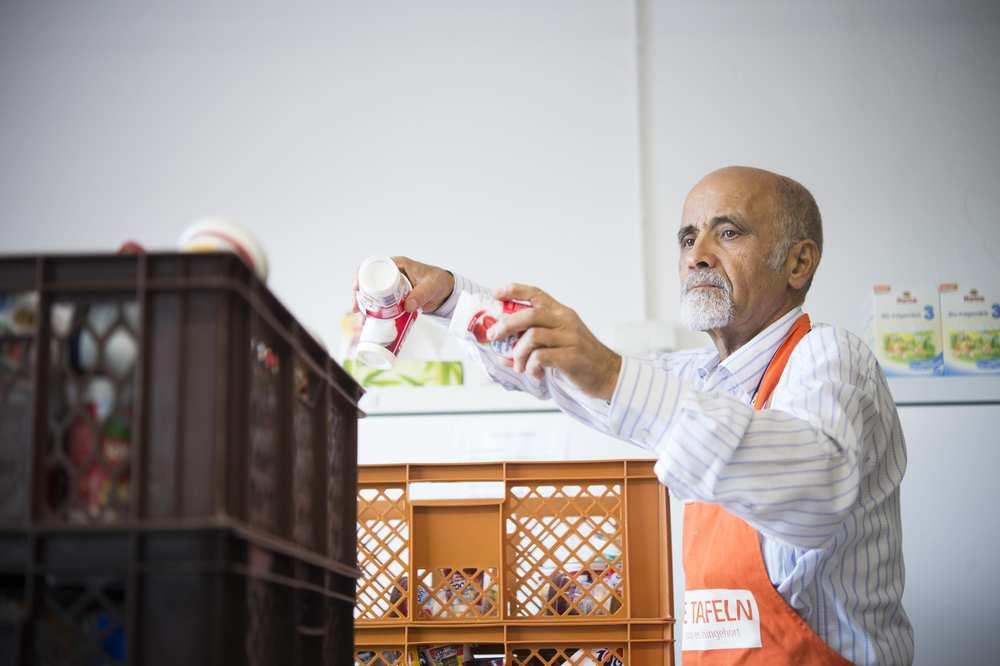 Ein Mitarbeiter der Tafel legt Joghurtbecher in eine Plastikbox.