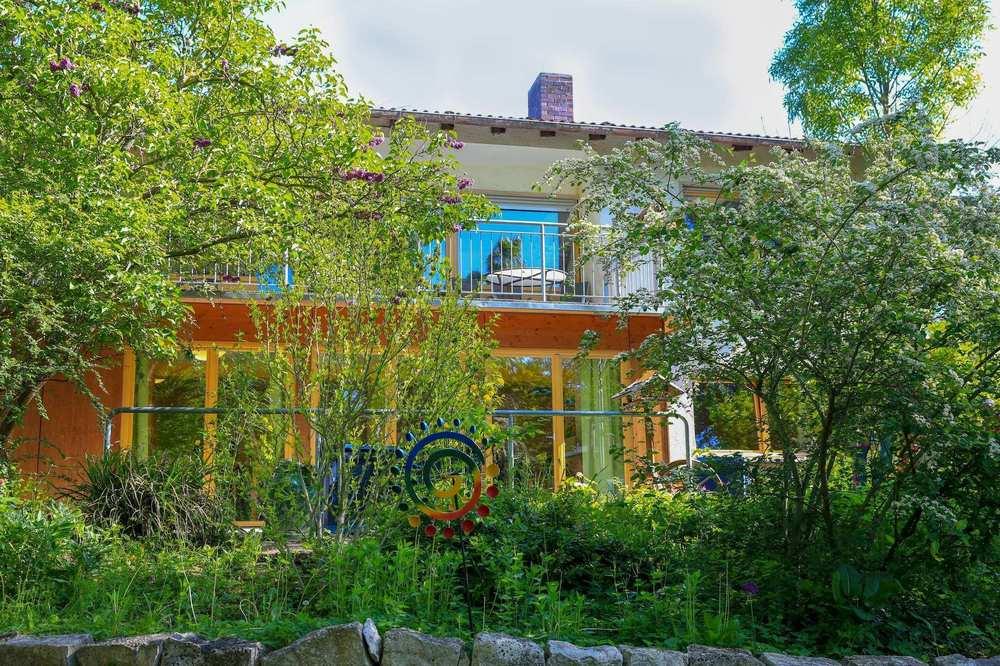 Hinter blühenden Bäumen und Büschen steht das großräumige und helle Gebäude der Tagespflege.