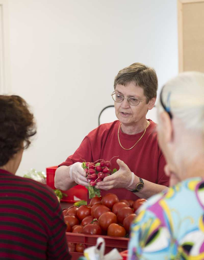 Eine Mitarbeiterin der Tafel gibt Radischen und Tomaten an wartende Personen aus.