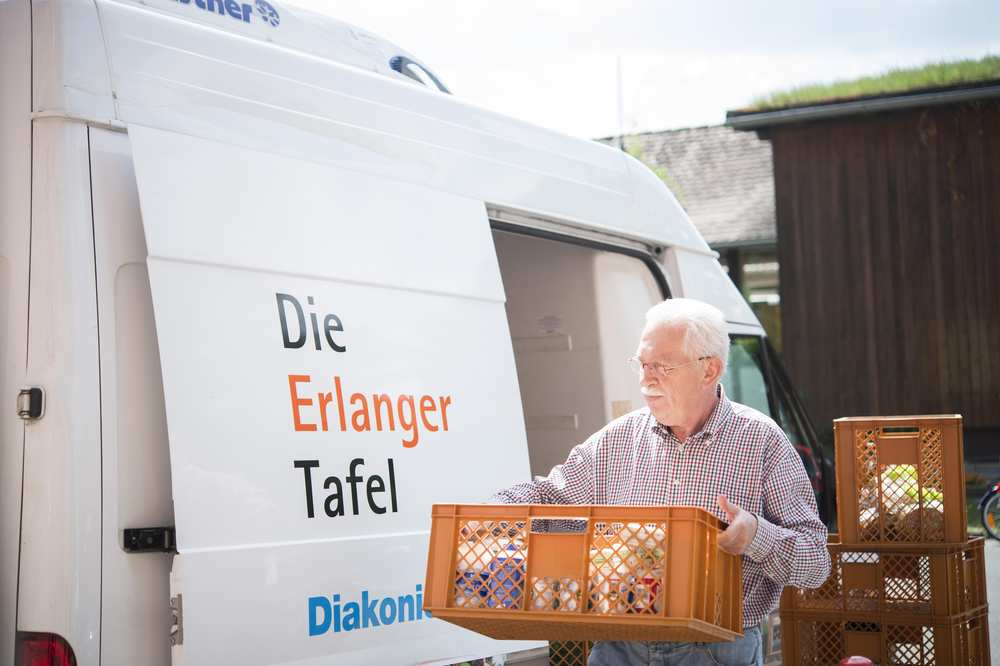Ein Fahrer der Erlanger Tafel lädt Lebensmittel aus seinem Lieferwagen aus.