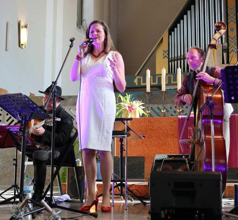 Eine Sängerin und zwei Männer mit Gitarre und Kontrabass musizieren im Altarraum.