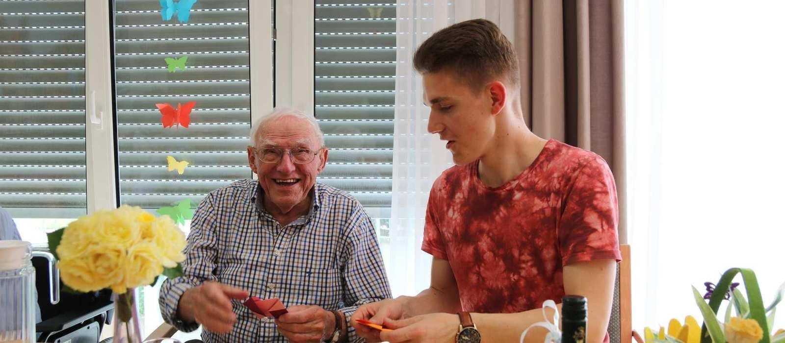 Ein älterer Bewohner und ein junger Mann sitzen an einem Tisch und spielen Karten.