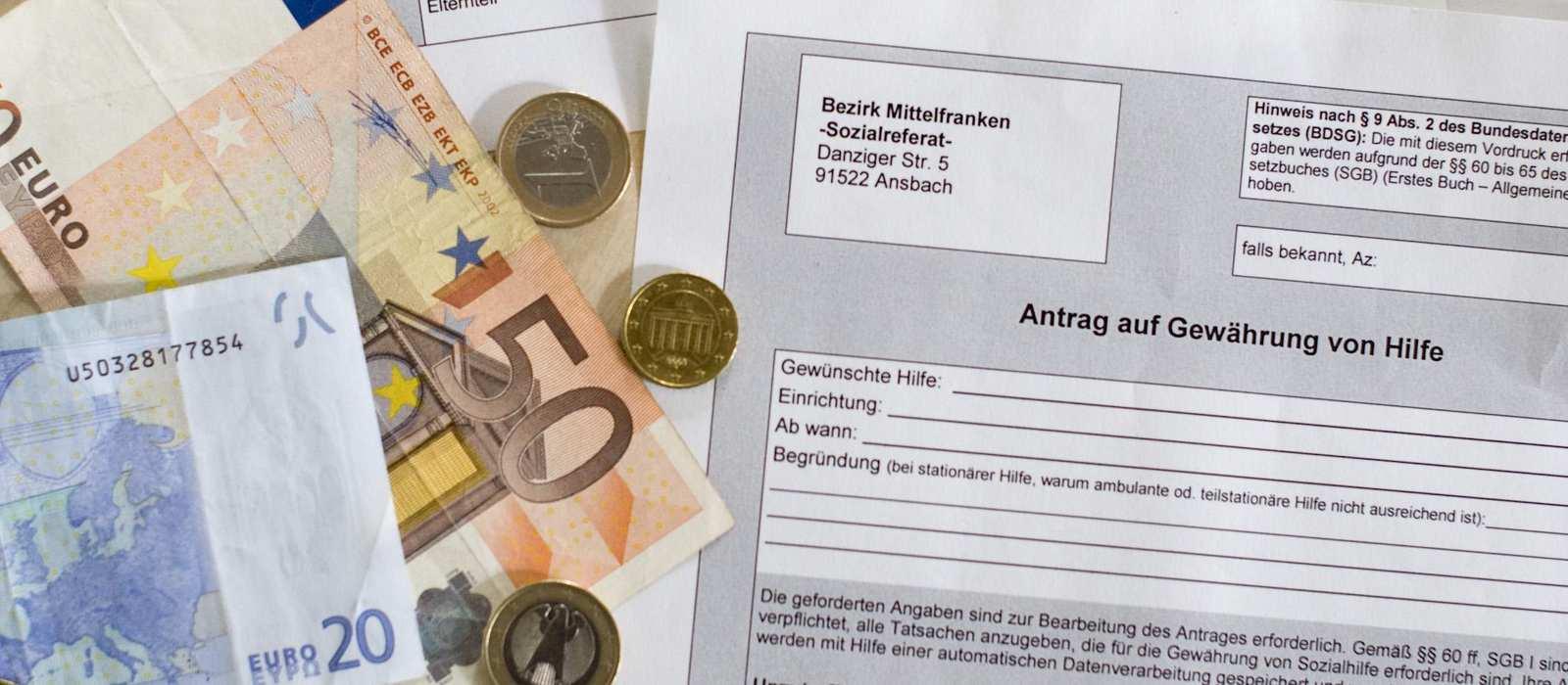 Ein zwanzig- und ein fünfzig Euro Schein liegen aus einem ausgedruckten Antrag.