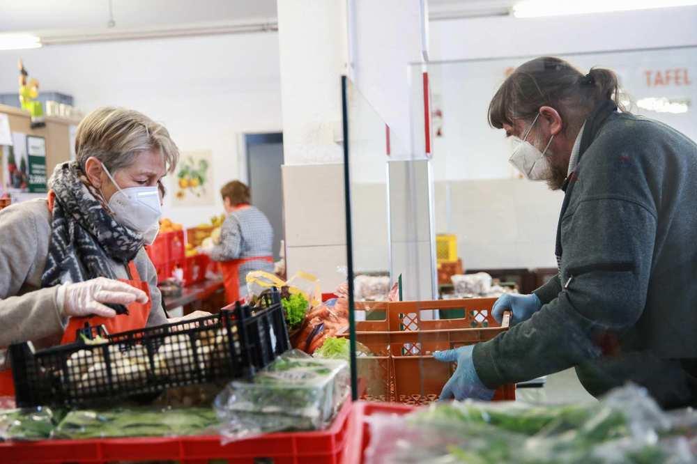 Zwei Mitarbeitende sortieren Lebensmittel.
