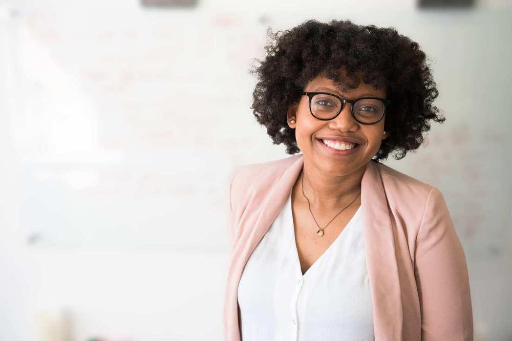 Eine junge Frau mit Brille und gelockten Haaren.