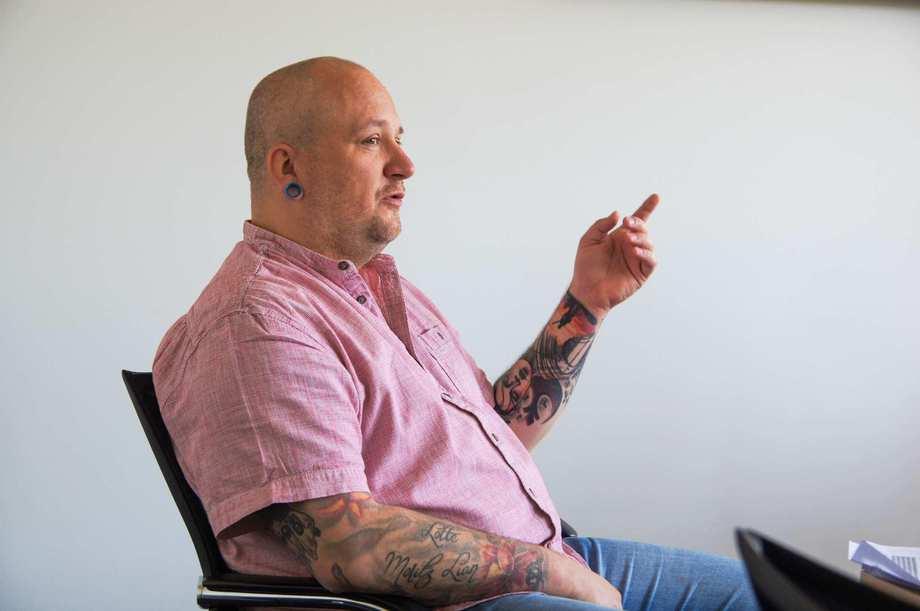 Ein jüngerer Mann im Hemd sitzt auf einem Stuhl und spricht. Beide Arme sind großflächig tätowiert.