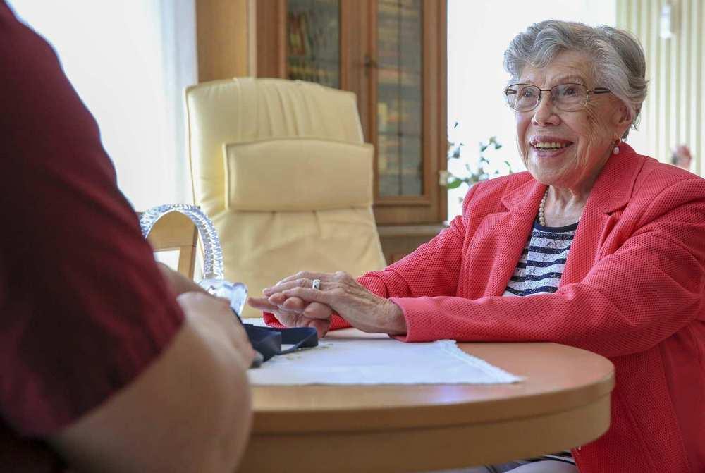 Eine ältere Frau mit Brille sitzt an einem runden Tisch und spricht mit einer Pflegekraft.