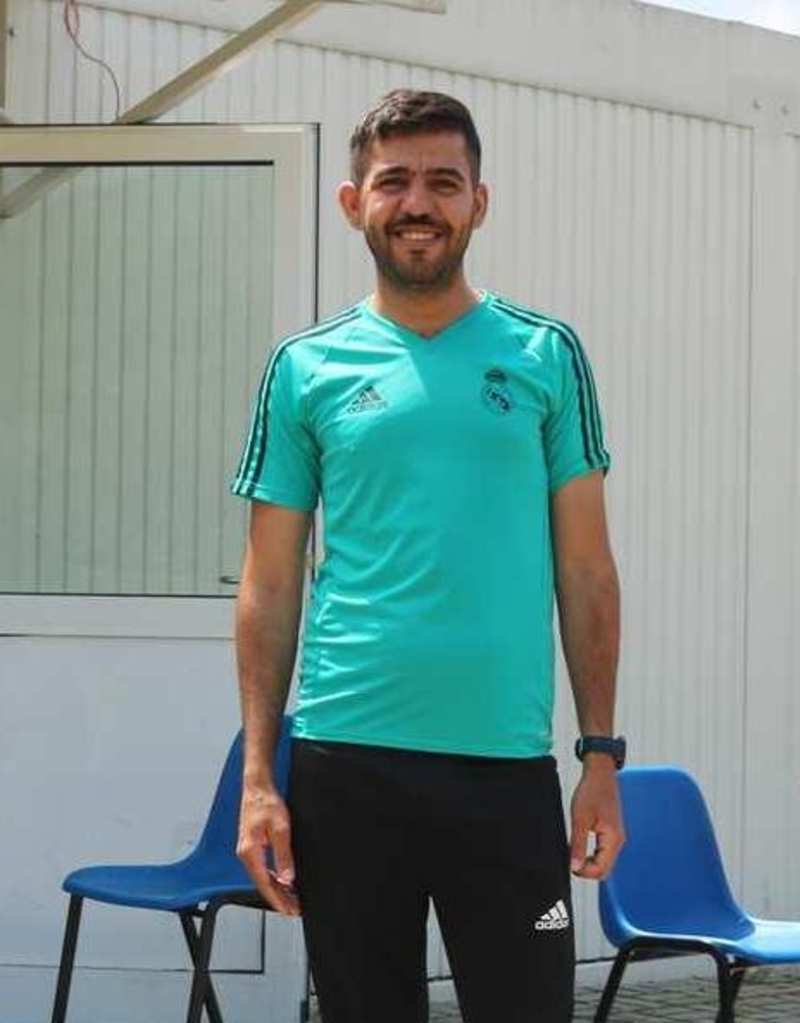 Ein junger Mann in Sportbekleidung steht vor einem Wellblechcontainer. Hinter ihm befinden sich zwei Plastikstühle.