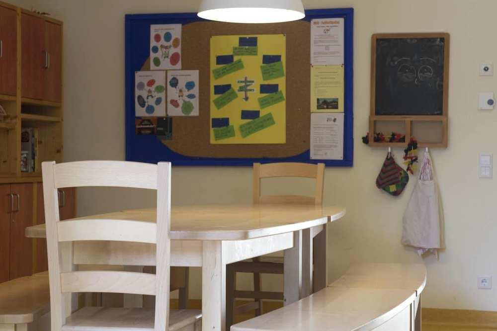 Tisch, Stühle sowie leicht geschwungene Sitzbänke aus hellem Holz.