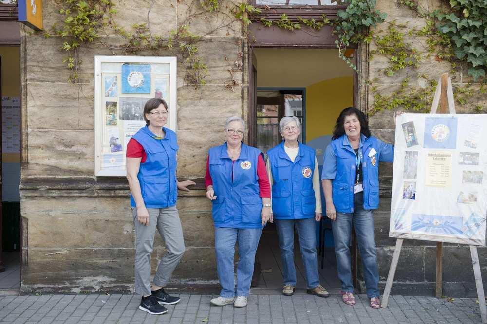 Vier Mitarbeiterinnen der Bahnhofsmission stehen mit ihren blauen Westen vor den Räumen am Gleis 1 des Erlanger Bahnhofs.