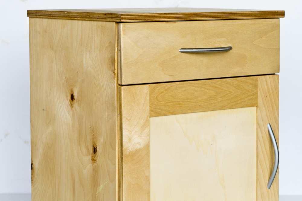 Ein Nachtkästchen aus hellem Holz mit einer Schublade und einem größeren Fach.