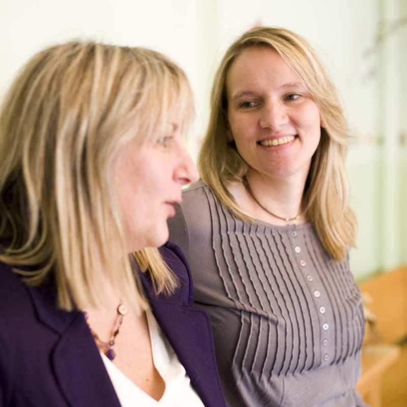 Zwei junge Frauen befinden sich im Gespräch.