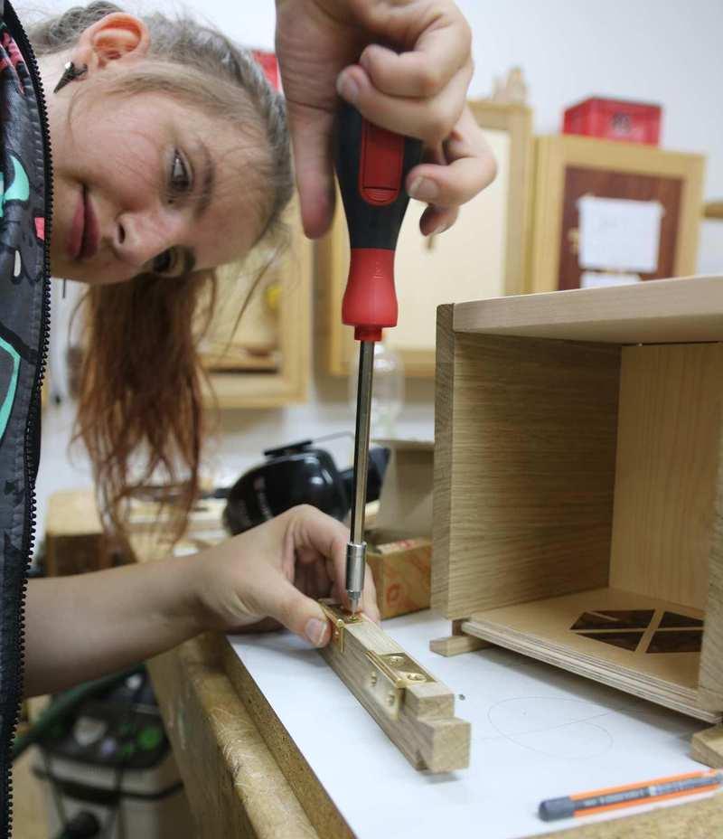 Eine junge Frau dreht mit dem Werkzeug eine Schraube fest..
