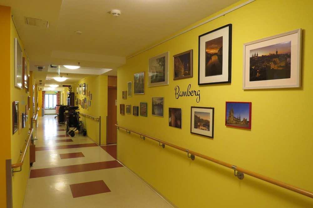 Ein Flur mit vielen gerahmten Bildern an der Wand.
