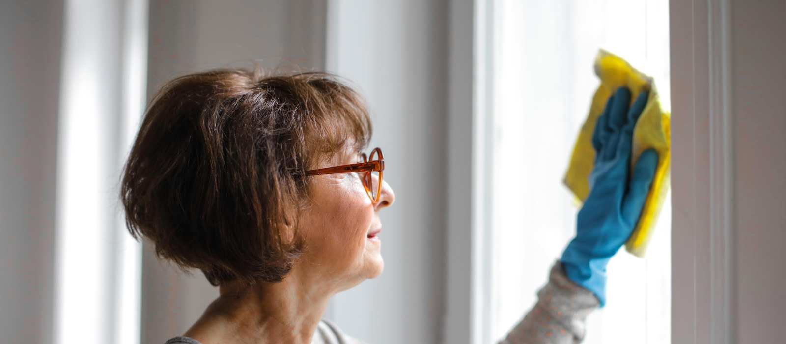 Eine Frau mit Gummihandschuhen putzt ein Fenster. In einer Hand hält sie eine Flasche mit Glasreiniger.