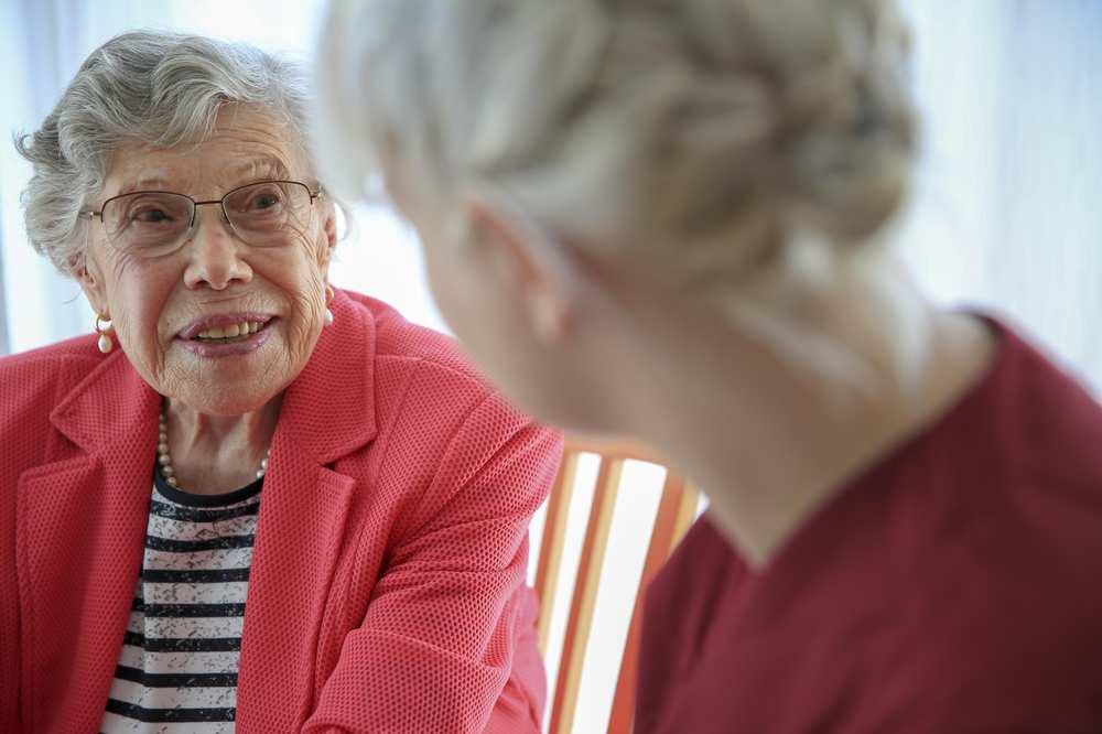 Eine Pflegekraft und eine ältere Frau im Gespräch.